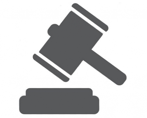 A courtroom with a judge and their gavel with plaintiff and defendant